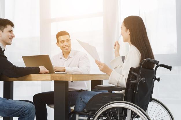 mujer discapacitada sentada en una silla de ruedas en una reunión de trabajo
