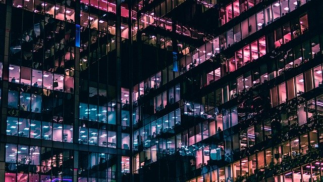 edificio de oficinas por la noche con algunas plantas encendidas